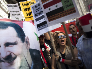 "Claudia Salmeh, a Syrian born American who supports President Bashar al-Assad, chants ""No More War,"" as fellow activists hold an image of Assad during an anti-war rally in Times Square, New York"