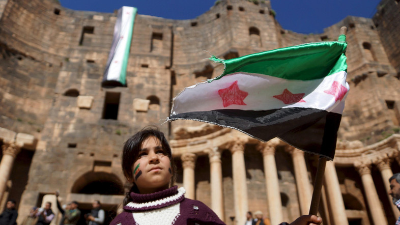 A girl waves an opposition flag during an anti-government protest inside a 2nd century Roman amphitheater in the historic Syrian southern town of Bosra al-Sham, in Deraa