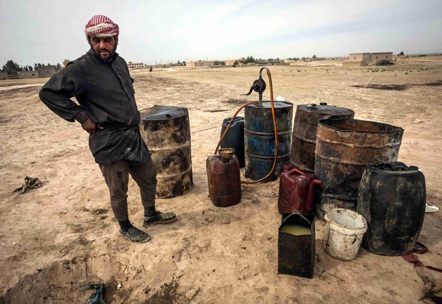 A Syrian man tries to refine crude oil in the Al Raqqa countryside in April 2013 (AFP)